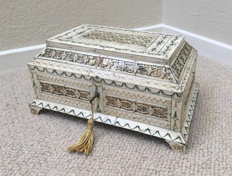 Early 19th century Russian stained and carved Bone Table Casket Kholmogory, veneered with panels of foliate engraved stained bone alternating with geometric and foliate fretwork panels over foil, raised on bracket feet.