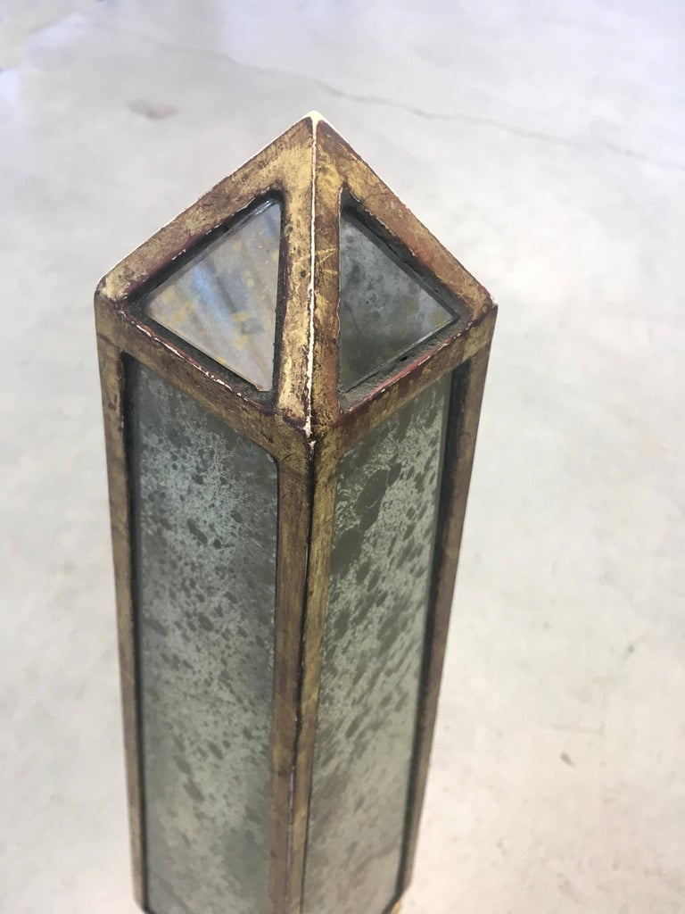 Pair of Classic obelisks composed of antique gold mirror with rubbed white gold leaf armature on ball feet atop plinth base.