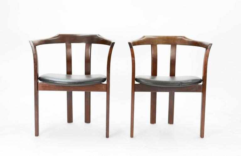 A handsome, comfortable and inviting pair of mahogany office or occasional armchairs with black leather seat cushions recently imported from Denmark.  Measures: Arm height is 27.5 inches.