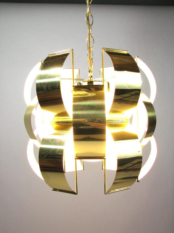 """Polished brass """"ribbons"""" enclose a single lamp in an opaque white globe at the center of this iconic Mid-Century Lightolier pendant light - an homage to 1960s lighting designer Max Sauze. The soft atmospheric glow and open downright make"""