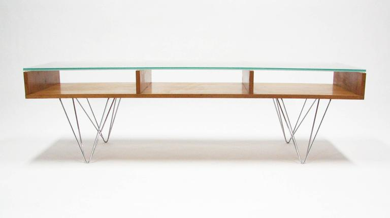 A cherrywood cocktail table with a frosted glass top over three open compartments on chromed, double hairpin legs. Origination: Postmodern architectural, interior design and furniture firm Bobo Modern Living, Boulder, Colorado (featured on 'Oprah'