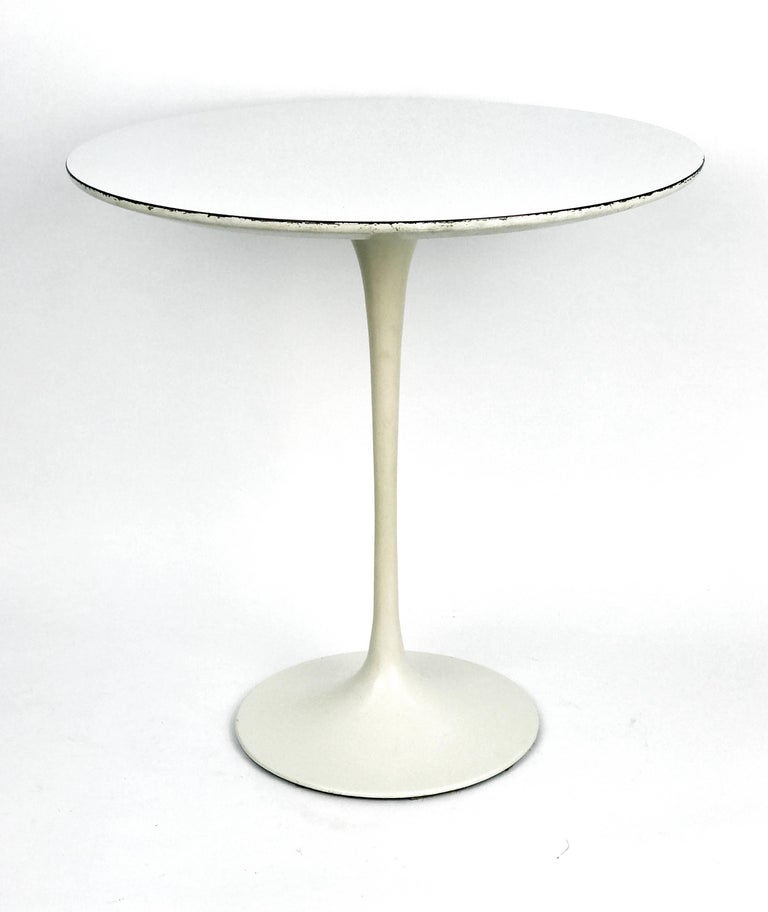 An iconic tulip side table with a white laminate top and a pale antique white enameled cast iron base by Eero Saarinen for Knoll. Model #160, circa 1957.