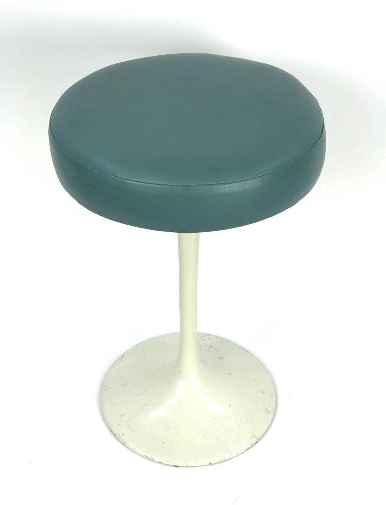 A classic and early tulip stool designed by Eero Saarinen for Knoll.  Newly reupholstered in deep aqua vinyl on an enameled cast iron base. (Knoll label lost during reupholstering).