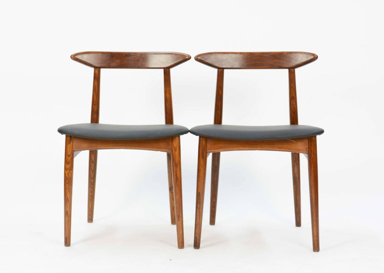 A wonderful set of 4 Danish Teak Dining Chairs After Hans Wegner .  The seat have been upholstered in a faux leather.