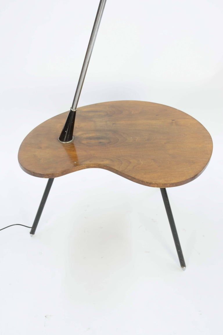 An atomic lamp table from Denmark with walnut table. An imported Danish floor lamp with a walnut biomorphic table top and a through angled leg to an amber globe. The tabletop is shaped like a painter's palette, 6