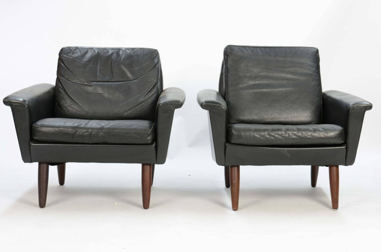 In a wonderful style and form are these handsome and comfortable club chairs imported directly from Denmark. A pair of iconic Danish club chairs in saddle leather after Fritz Hansen.