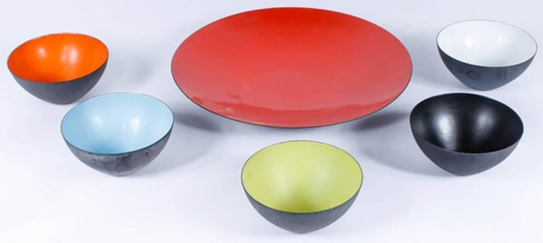 A set of six Krenit bowls and a serving dish attributed to Herbert Krenchel (for Torben Orskov, Copenhagen), circa 1955.  The round bowls and larger serving dish are made of black metal, with colorful enameled interiors. The large serving dish is