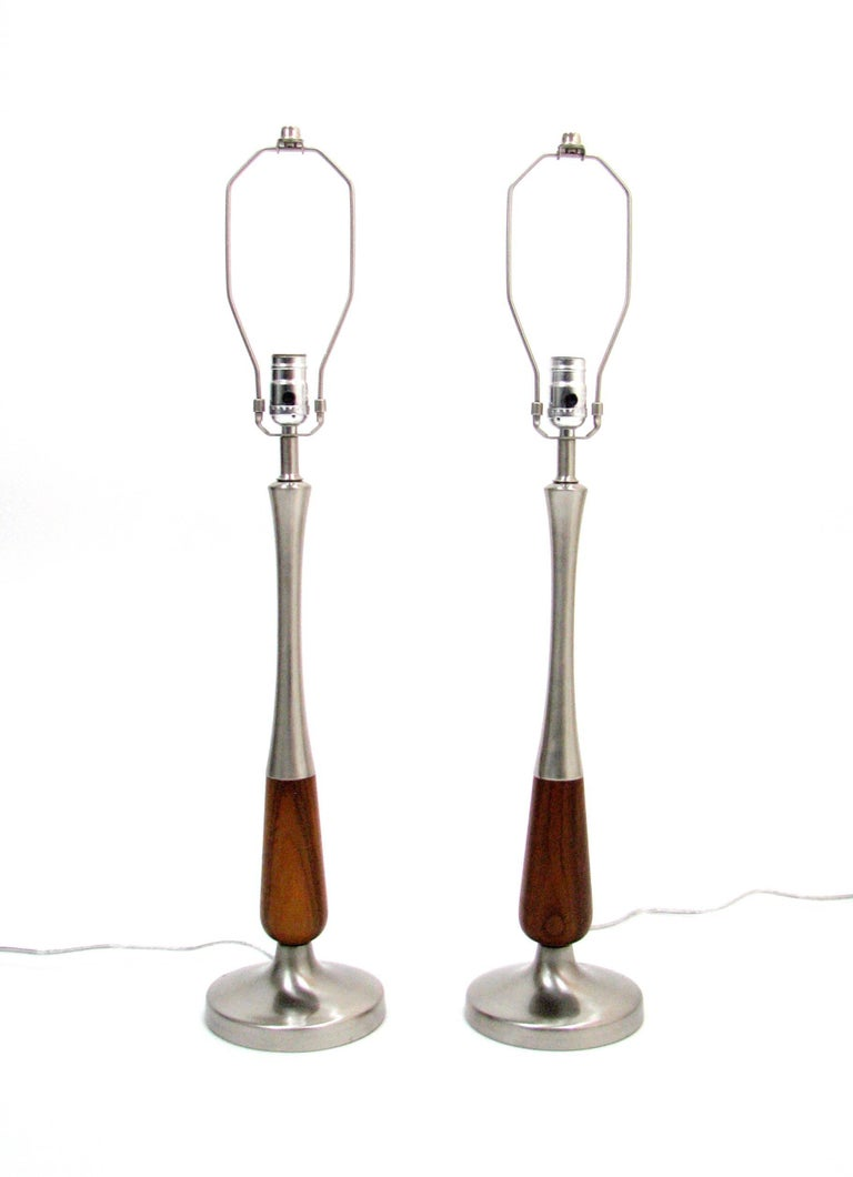 A beautiful pair of Midcentury walnut and brushed nickel lamps.  Originally plated in brass, the molded steel sections have been re-plated in brushed nickel and the walnut has been refinished for new life in the 21st century.  These lamps are 20