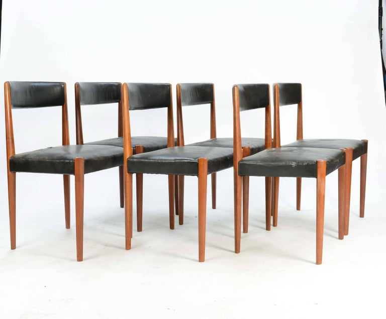 A set of six sculpted dining chairs by Aage Christensen for Fritz Hansen that features the sculpted diamond legs and distressed leather seat. These chair are elegant and understated in their refinement. These are Fritz Hansen model 4112.
