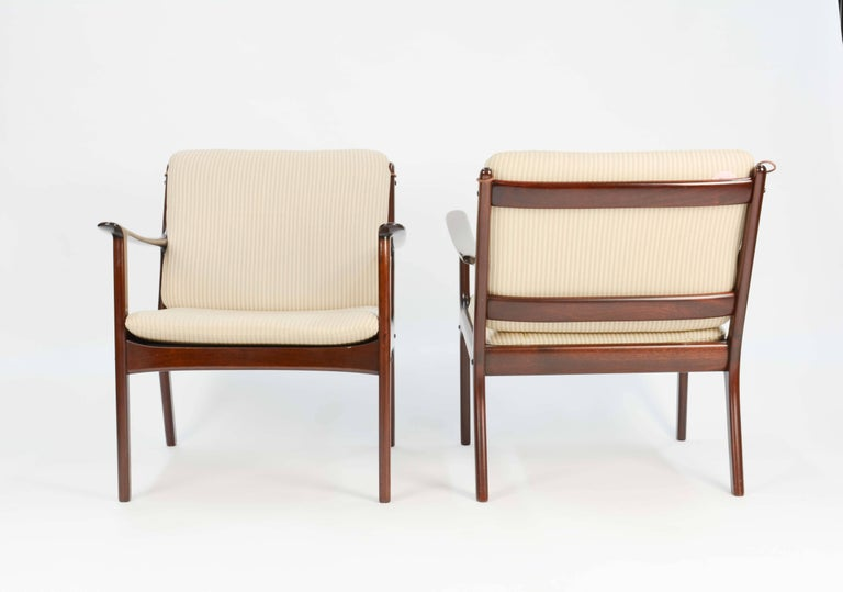 A pair of Ole Wanscher's club chair JP112 for P. Jeppesens Møbelfabrik of Denmark in mahogany with pin stripped fabric.