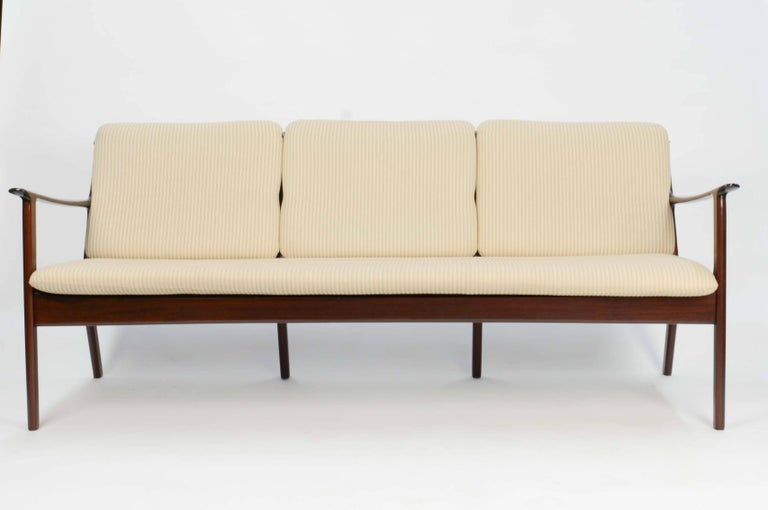 Ole Wanscher's sofa JP112 for P. Jeppesens Møbelfabrik of Denmark in Mahogany. The three-seat sofa features the detailed design of the farther of Danish modern movement.