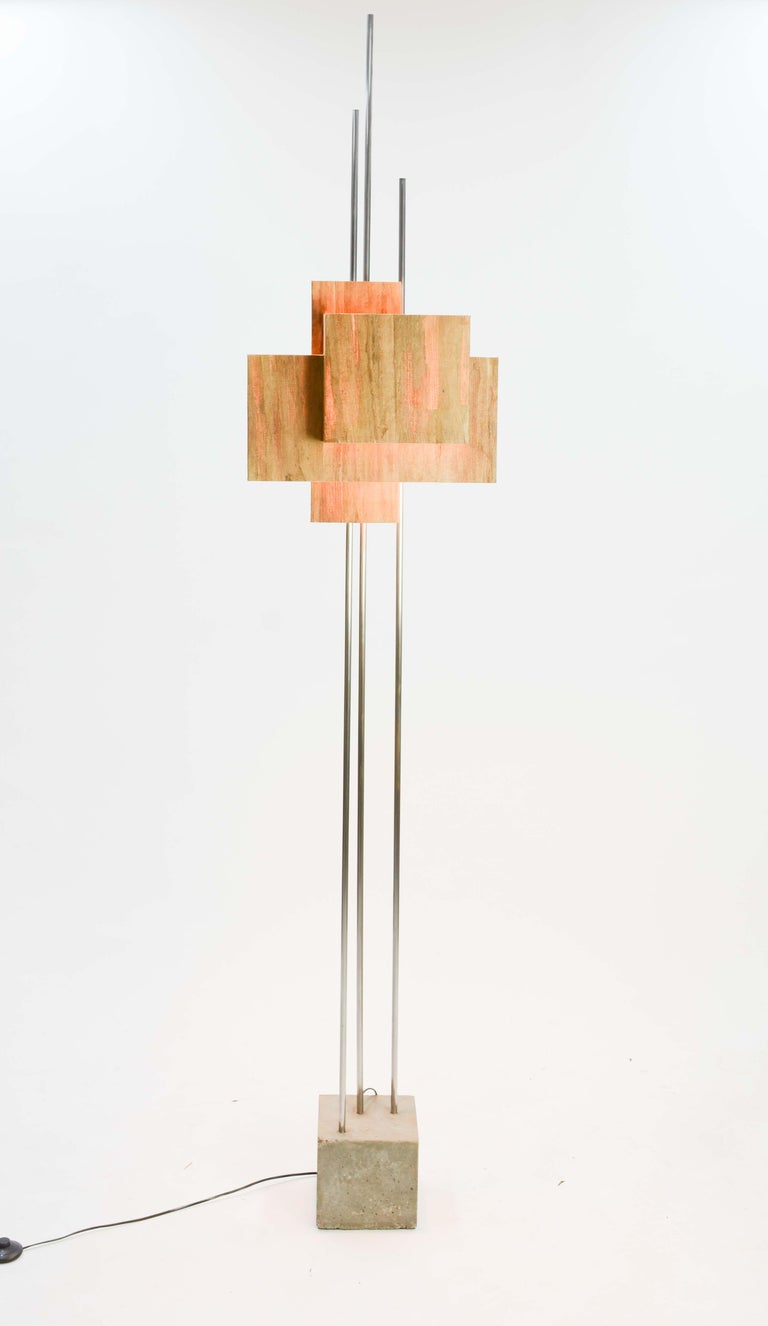 This Architecturally inspired floor lamp echoes the light work of FLW and the concrete of Prouve. It is a wonderful and playful combination of the weighted concrete and the light of the banana paper shade. The trio of aluminum uprights tie the two