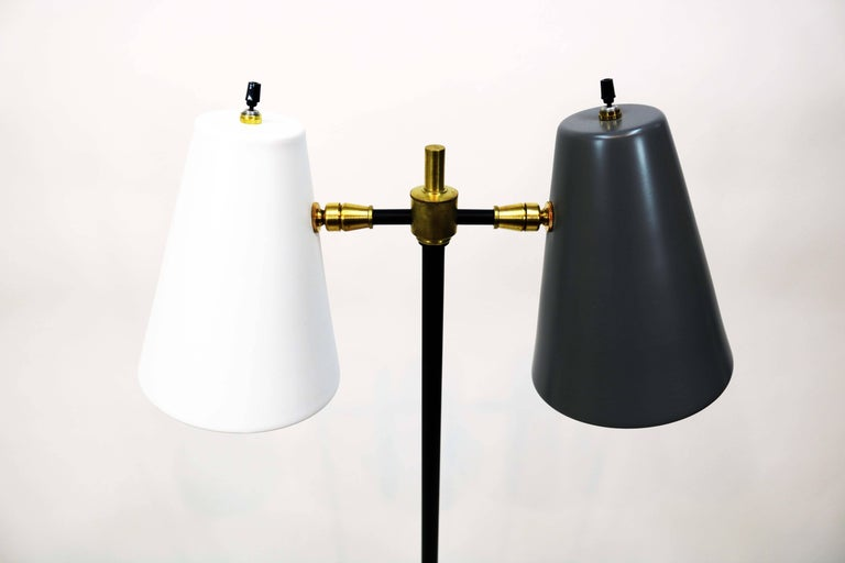 A recently restored midcentury double cone floor lamp. One cone in white, the other in charcoal on a black painted metal base with brass detail. Provenance unknown.