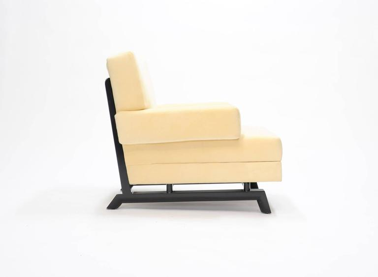 """A wonderful pair of Paul Laszlo club chairs for Brown and Saltman of California. On the Laszlo iconic sled base and tapper foot. The chairs are done in a cream fabric and the frames have been ebonized black. Arm height is 20""""."""