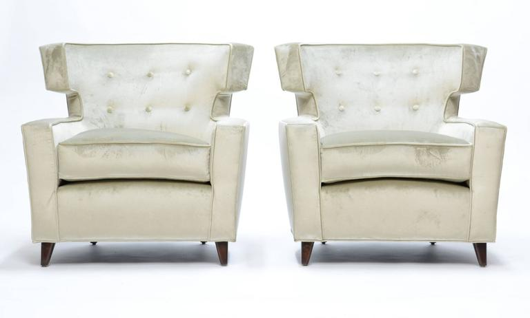 "A beautiful pair of wingback club chairs in the manner of Gio Ponti, freshly upholstered in a velvet chenille, with very light green hints in the fabric color.  Walnut legs.  Arm height is 20"" H."