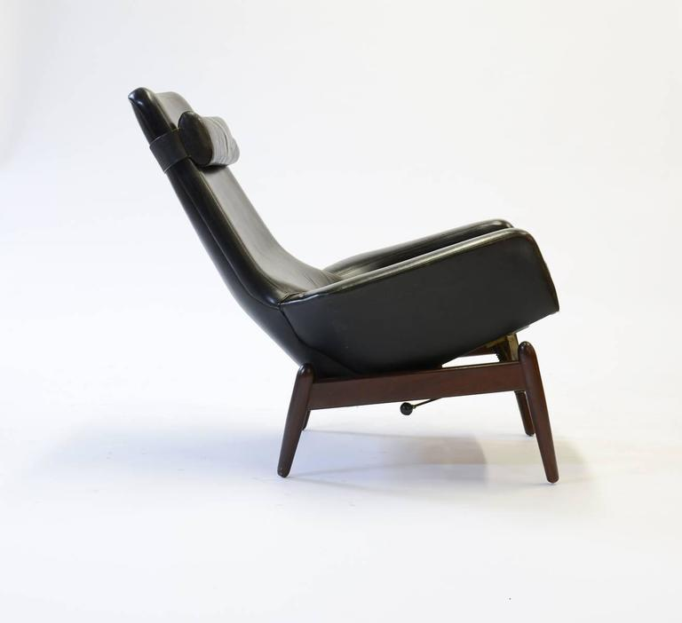 A wonderful example of Kofod-Larsen work for Povl Dinesen, circa 1960. The chair has the rare tilting handle for eight comfortable reclining positions. The leather is original and distressed. The chair tub floats above the frame, giving it a