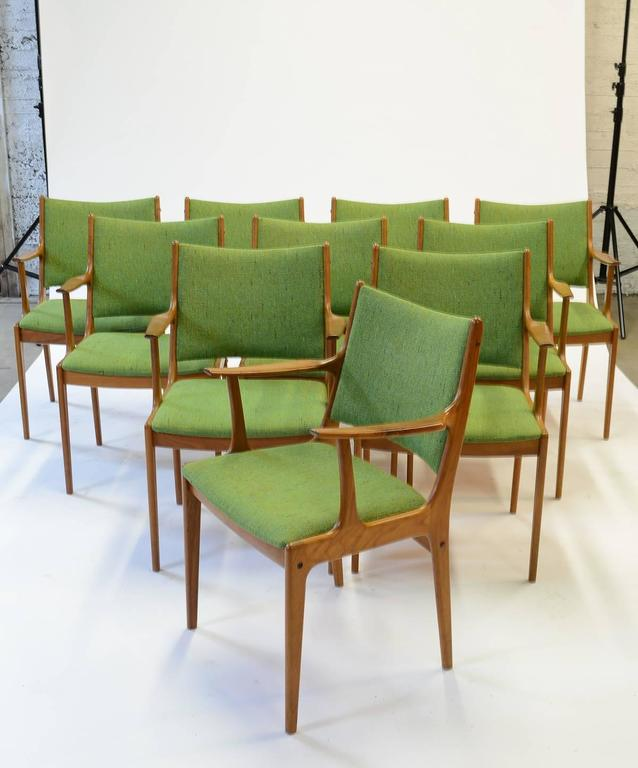 An Impressive set of Johannes Andersen armchairs for Uldum Modelfabrik with green fabric by Nanna Ditzel Hallingdal. The full set of ten armchairs are crafted in teak.