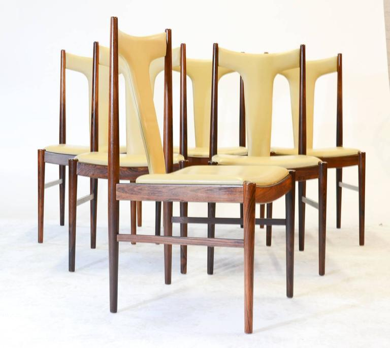 Six rare and magnificent high back dining chairs in rosewood and butter leather by Arne Vodder for Sibast of Denmark. Vodder's classic style mimicking natural forms is present here in the simple, yet dramatic slope of the back support.