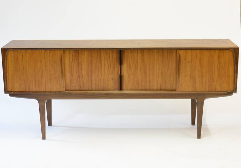 A magnificent Danish teak Mid-Century sideboard with highly-serviceable center compartment drawers, a shelf each in the left and right compartments, and distinctive-styled curved handles on the sliding door panels.