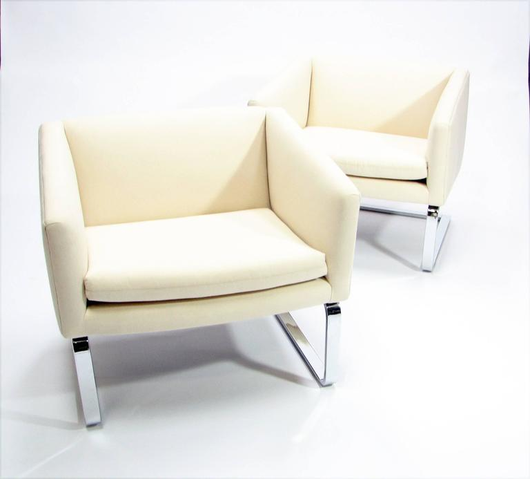 A sculptural pair of Mid-Century club chairs with chrome bases and reupholstered in cream muslin.