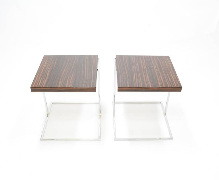 A pair of stunning zebra wood and chrome cantilever side tables. Their graceful cantilever design delivers strength, symmetry and simplicity while the zebra wood tops perfect each one with complimentary but unique natural patterns and shading.