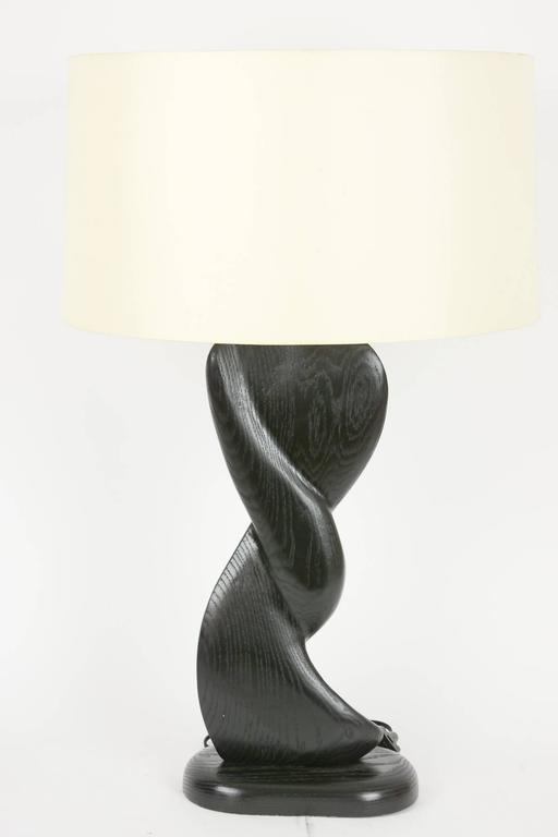 A pair of French oak, cerused black lamps, hand-carved with sensual curves.
