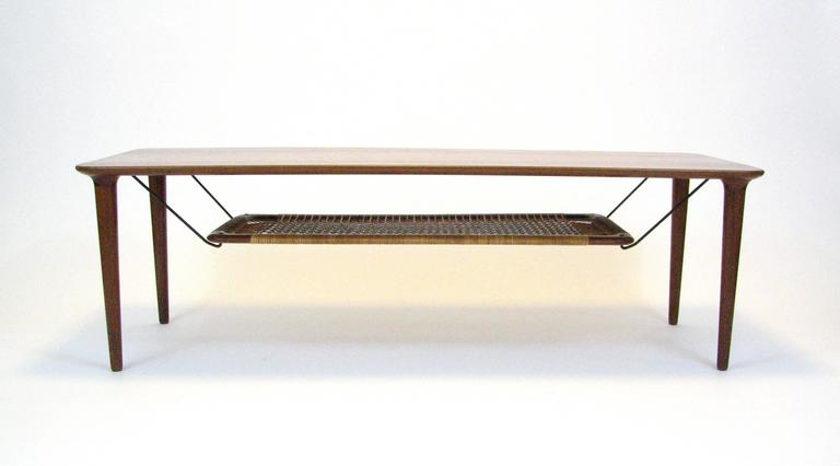Mid-Century teak coffee table with cane magazine shelf by Gustav Bahus of Norway.  1960s.  Well-preserved overall condition. One broken strand of webbing, as pictured.  Please note:  Pick up for this table is in Denver, Colorado.