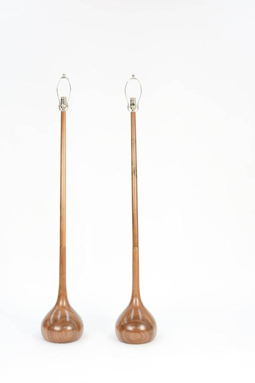 This pair of hand-carved European walnut tulip bulb floor lamps are the latest of 20th century Studio's own design work. The walnut grain patterns in these lamps is extraordinary, with graining unique to each lamp.  Please note: Lamp shades
