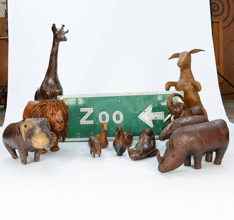 A 14 piece zoo, including Dimitri Omersa's hippo, rhino, pig, giraffe. kangaroo, lion, elephant, small rhino, elephant bank, two ducks, pig, and a ceramic sleeping cat, plus a zoo sign from California.
