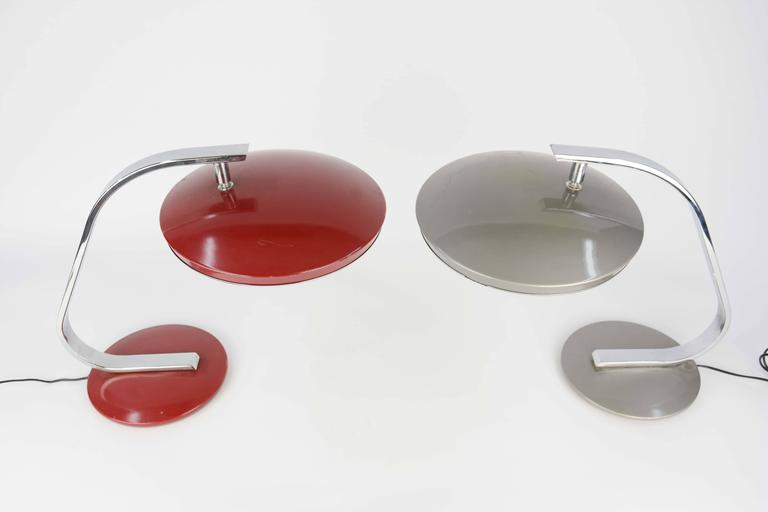 A matching pair of Fase table lamps in red and silver. Elegant chrome and enameled metal desk lamp by Fase Madrid, Spain, articulating head, two bulb set up behind original glass diffuser, on/off switch on the shade rim.