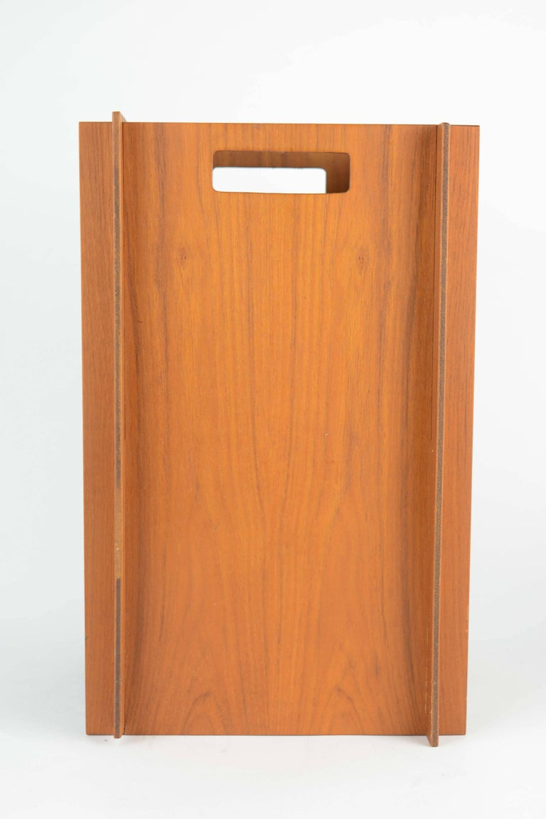 A playful waste bin or trash container from Denmark in teak with interlocking sides and cut-out handles. A fine example of Danish wood working skills and attention to details. bin is unmarked.