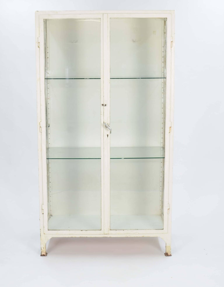A wonderful Industrial double bank Medical cabinet with locking double doors and two glass shelving. The doors are functional and back wall has a row of hanging hooks for display. This piece is solid steel and has the build quality of 1940s metal