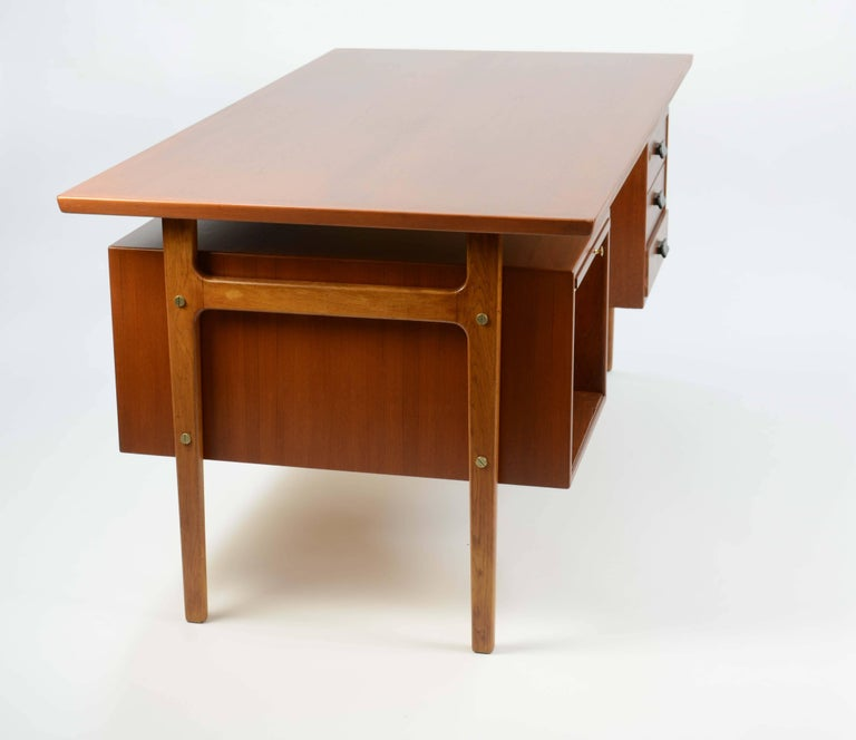 A handsome and stately executive desk by Torben Strandgaard for Falster Mobler of Denmark. The desk features brass accents and the front bookcase.