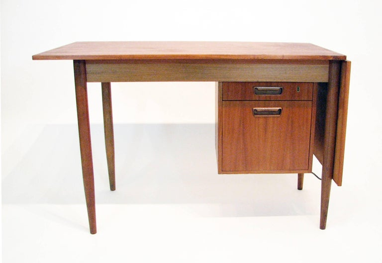 This Mid-Century teak and rosewood writing desk by Gunnar Nielsen Tibergaard is simply and ingeniously versatile. The hanging drawer cabinet, including one smaller and one file-size drawer, can be moved to the left or right. The drop-leaf also