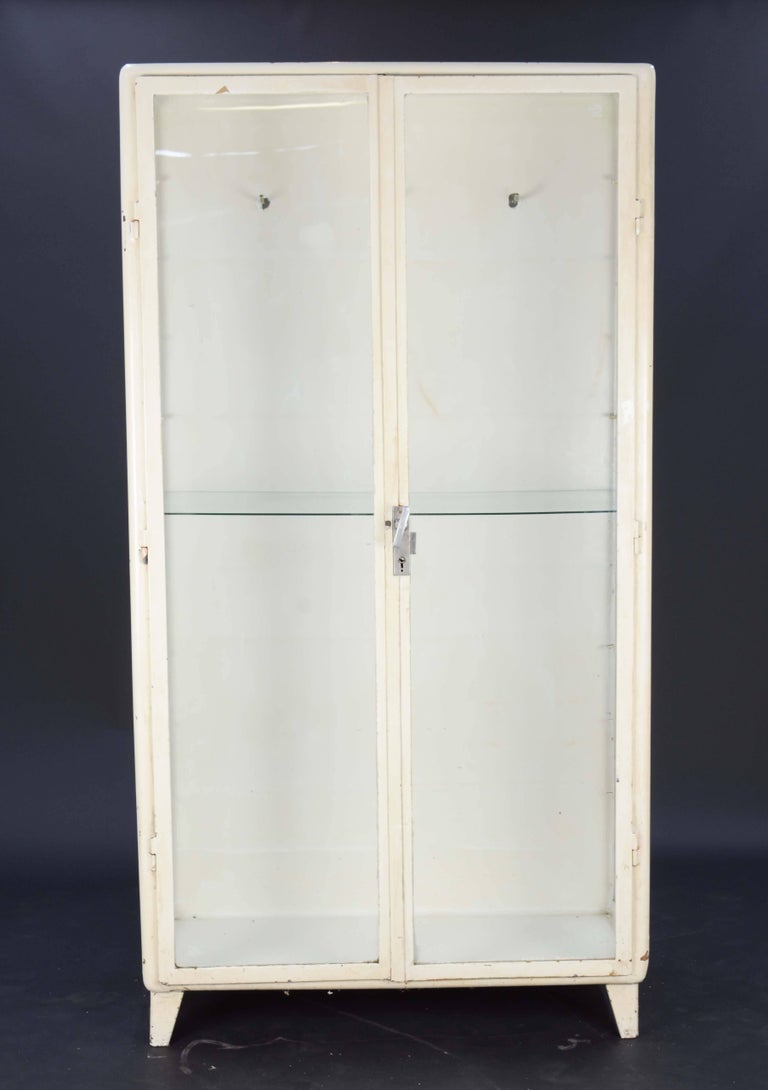 A 1940's Eastern European Medical Cabinets. A wonderful cabinet to display all your treasures.  They both have the original hardware and lock with a keys.  It comes with 2 adjustable glass shelves. and rear cabinet hookers