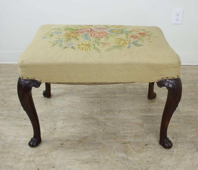 A decorative footstool with its original intricately embroidered seat and finely carved mahogany legs. The claw feet on this piece are particularly well articulated. The seat has good loft for a piece of its age. Sturdy and would make a nice