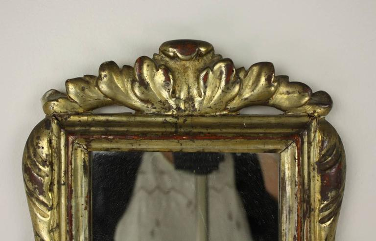A turn of the 19th Century Baroque gilded mirror from Italy with stylized lush leave details and very good red show-through.  Some wear on the mirror adds to the look.  The smaller size makes this piece perfect for the powder room or a small