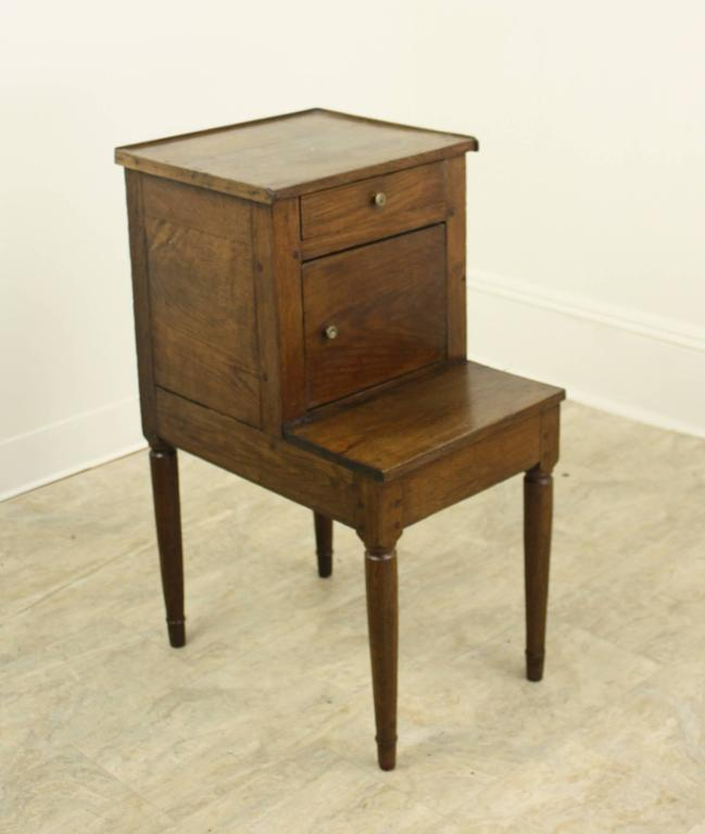 A charming side cabinet or nightstand with sweet design details such as galleried top and nicely turned legs.The depth of the top section is 12