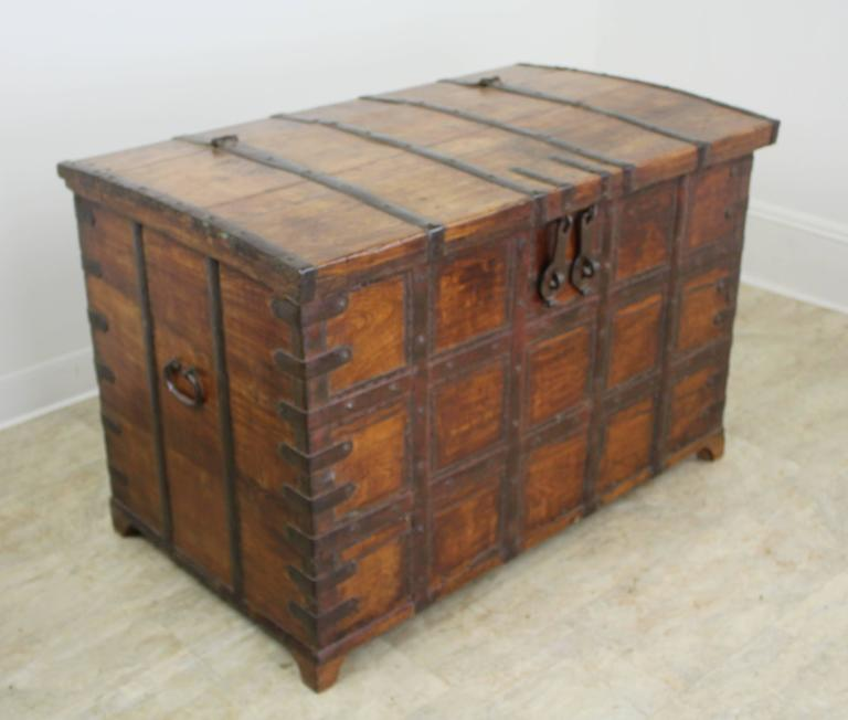 An early French trunk or blanket chest, with highly decorative iron strapping and hand-wrought iron handles. The front and sides of the piece have their original stain and vanish, worn to a glow. The arched top also has great patina and natural