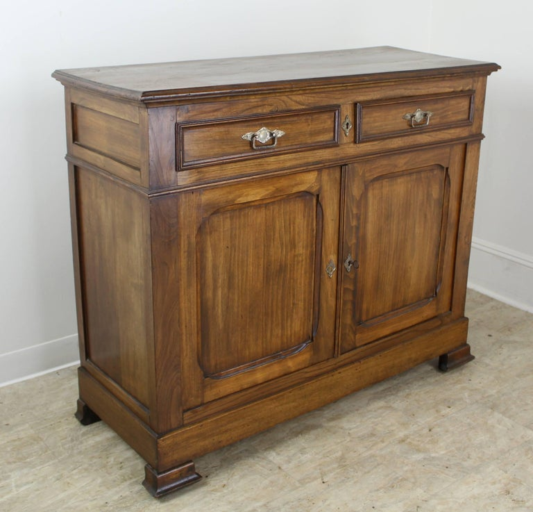 A classic two-door buffet in dramatically grained elm. The eye catching design details include interesting molding at the top, carved inset panels on the doors and sides, and classically shaped feet. The single interior drawer is non-adjustable.