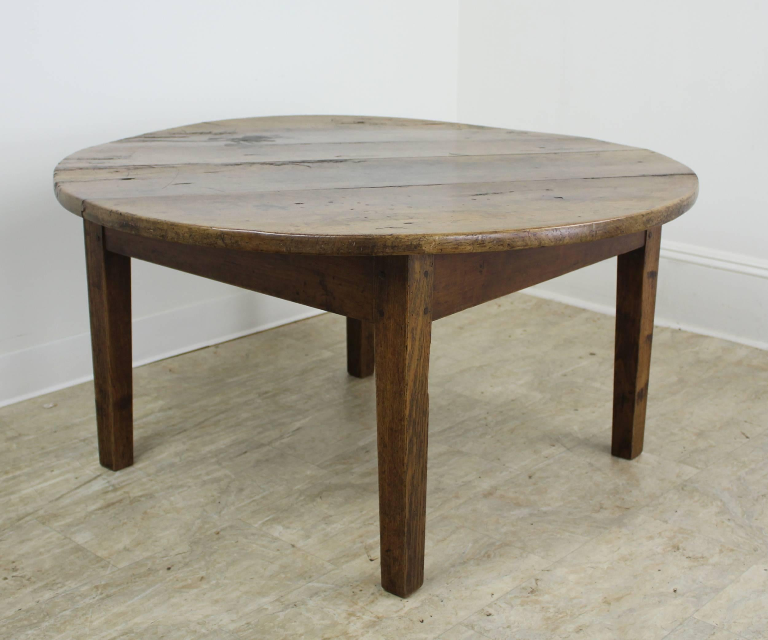 A Charming Round Cherry Coffee Table With Chunky Legs And Top. The Top Has  Some
