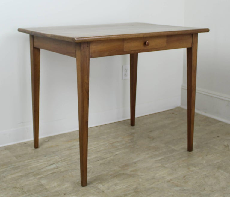 A pretty writing or side table in light walnut with a dramatically grained top. The thin tapered legs and high apron of 26 inches give this desk an elegant silhouette that would work with any decor. Image #6 shows the hand cut, naturalistic edge to