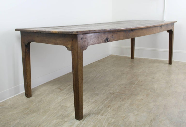 A long rustic pine farm table with glorious pine grain and natural knot holes. The color and patina on this piece are really good. With 92.5 inches between the legs on the long side, this table can seat ten. The apron height of 24.5 inches is good