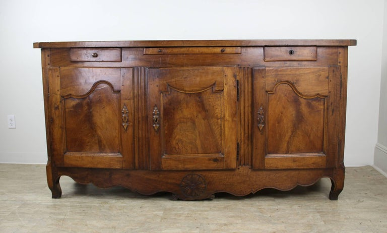 A handsome and imposing French walnut enfilade with interesting design detail and decorative carving at the well shaped apron. Graceful carved wood escutcheons and decorative reeding at the corners add another degree of period design interest. In