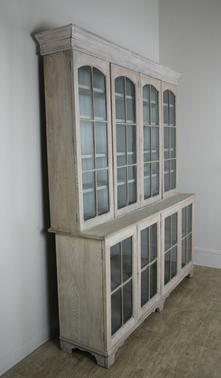 An elegant early English oak bookcase, bleached for a clean and modern look. Top and bottom components come apart for easy transport., with adjustable shelving top and bottom. The interior of this piece has been newly painted a serene light
