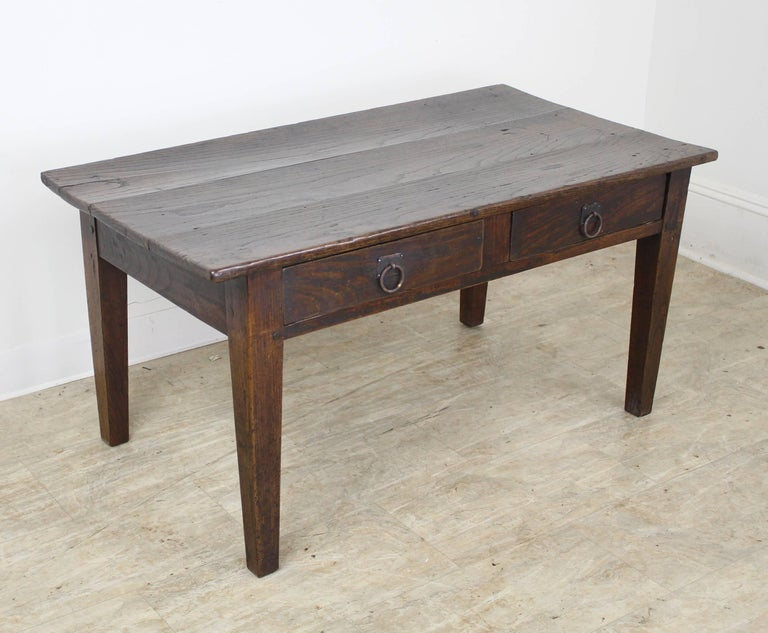 A sturdy and handsome dark chestnut coffee table, with two drawers for storage and visual interest. Wrought iron rings lend a rustic look. The chestnut has great grain and patina. Nice size for most rooms.