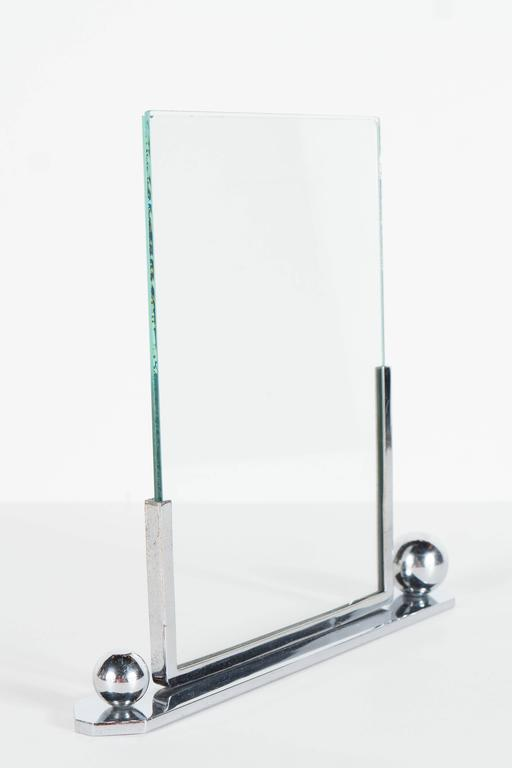 An Art Deco polished chrome picture frame with asymmetrical ball detailing. A hexagonal base supports a r partial chrome frame with differing side heights in which rest two beveled glass frame supports. This piece can support a photo or image 5 1/8