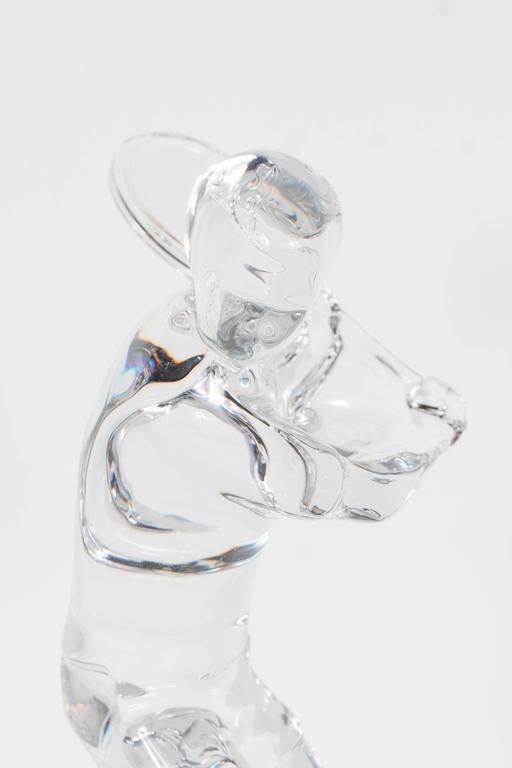 A Baccarat figurine depicting a tennis player preparing to hit a one-handed backhand. This would be a perfect sculpture for any tennis enthusiast, or for a sports lover looking for an elegant glass sculpture to adorn a cocktail table or office desk.