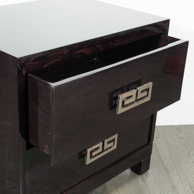 This stunning pair of Mid-Century end tables or nightstands were realized in the United States, circa 1950. They feature rectilinear bodies and volumetric square feet in hand-rubbed ebonized walnut fitted with two drawers each. They offer polished