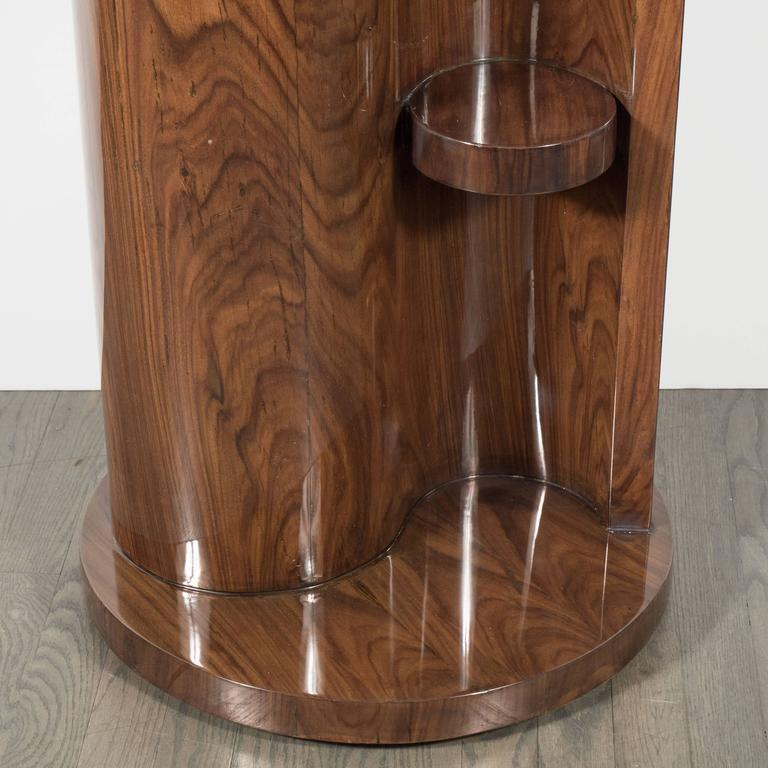 An Art Deco occasional table in bookmatched burled walnut. A round base supports a vibrio-shaped pedestal, which holds two miniature circular shelves half-way up its overall height. The top features intricate starburst detailing consisting of